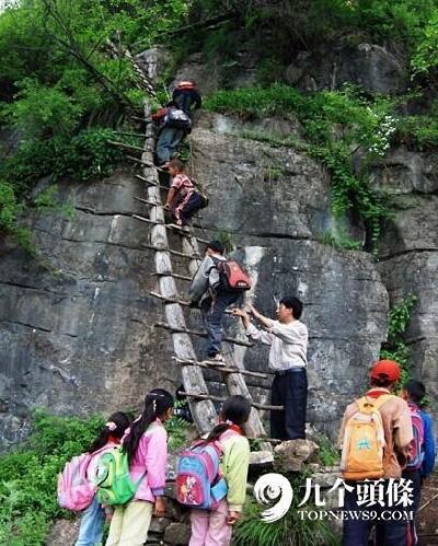 四川甘洛县,老师李桂林将孩子们一个个扶上摇晃的木梯.图片